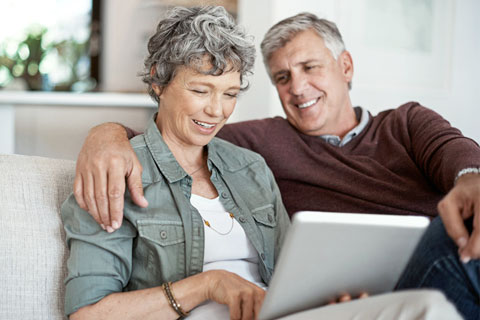 A happy couple is using the Affinity Patient Portal on a desktop computer