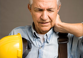 Construction worker with his hand on his neck in pain